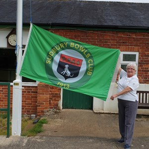 Club President Mrs Rachel Bonsor holding the new club flag, which she kindly donated to the club. An engraved brass plaque in recognition has been attached to the flag pole support.