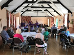 Visitors to Coffee and Chat enjoying a musical presentation by the Purple Group