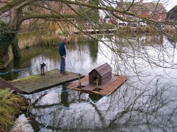 Councillor Clack prepares the duck house for placement in the centre of the pond