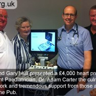 Darren and Gary Hull presenting a £4,000 heart probe to Consultant Paediatrician, Dr Adam Carter